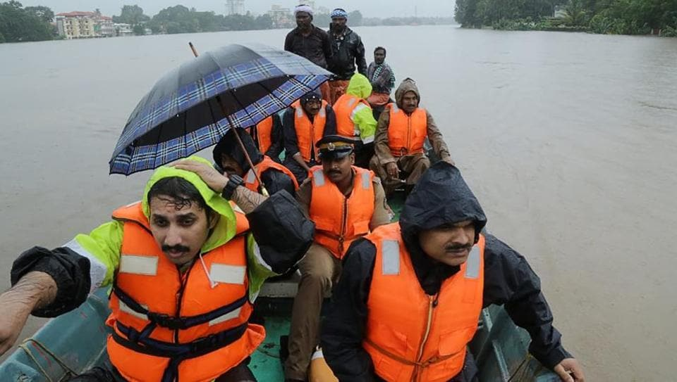 Indian fire and rescue personnel evacuate local residents in an boat flooded following monsoon rains at Aluva, Kerala.