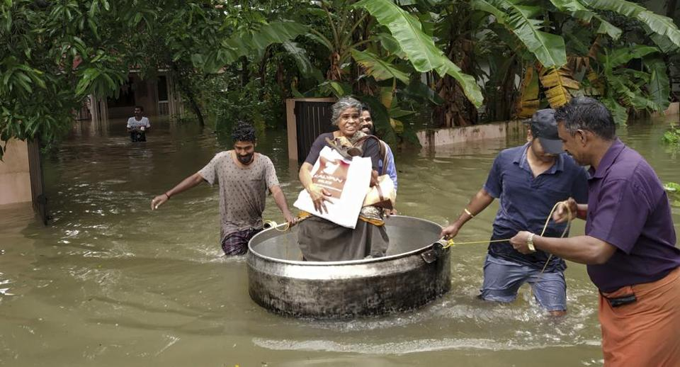 An elderly woman is rescued in a cooking utensil after her home was flooded in Thrissur, Kerala on Thursday.