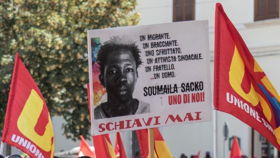 "Migrant workers hold a banner in honour of Soumaila Sacko, a migrant agricultural worker from Mali who died on June 2, during in a march in Foggia. The other dead came from Nigeria, Mali, Guinea, Ghana and Morocco. There is no suspicion of foul play in the crash, but Vaccaro believes the men were victims of the so-called ""caporalato"" system which exploits farm workers across Italy. (Roberto D'Agostino / AFP)"