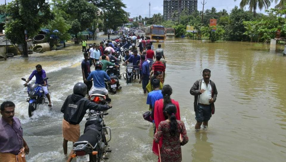 People move past a flooded road in Thrissur, Kerala, Friday, Aug. 17, 2018.