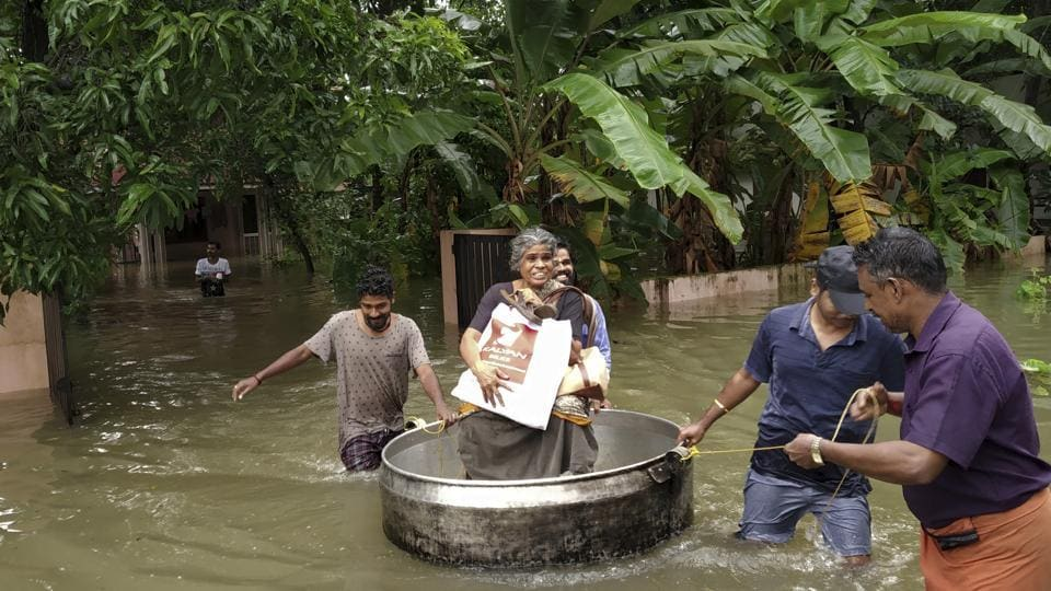 An elderly woman is rescued in a cooking utensil after her home was flooded in Thrissur, Kerala, on August 16, 2018. The torrential rains in Kerala have left over 30,000 people homeless, killed more than 160, destroyed crops and disrupted air, rail and road traffic within the state for a week. Different studies, however, have found that climate change and deforestation were the main causes of an increase in rainfall. (K.K. Najeeb / AP)
