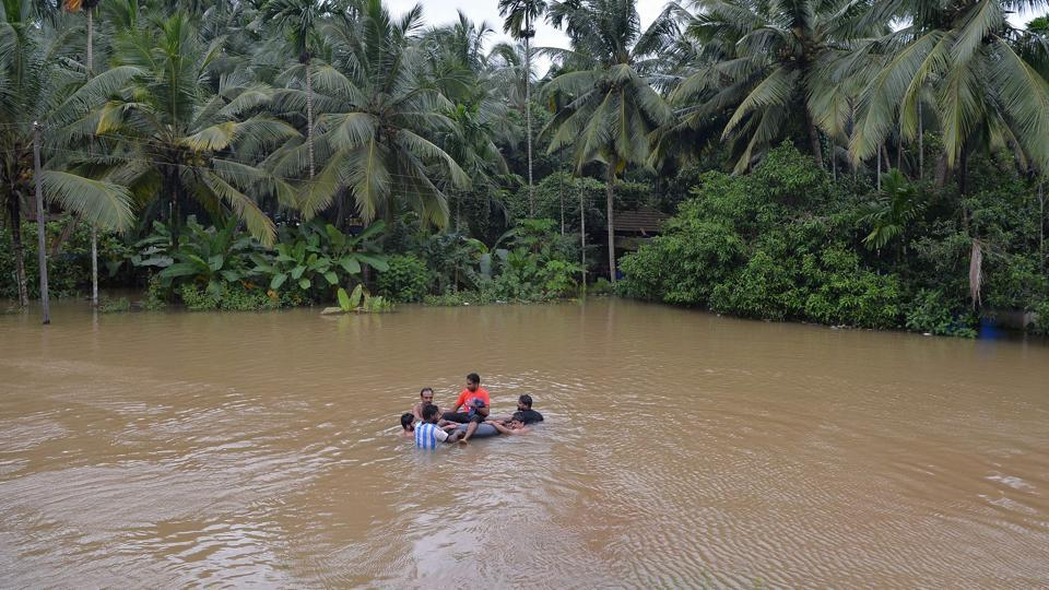 A group of residents cross flooded waters on an inflated tube in Kozhikode district.