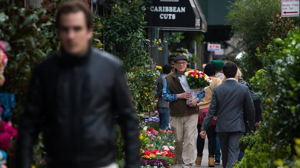A customer carries roses in Manhattan's flower district in New York, U.S. Photographer: Michael Nagle/Bloomberg