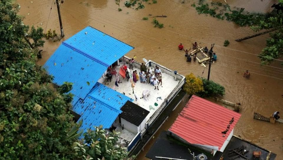People wait for aid on the roof of their house at a flooded area in Kerala, August 17, 2018. REUTERS/Sivaram V