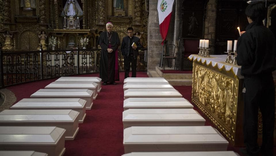 "Ayacucho's Bishop Salvador Jose Miguel Pineiro, left, stands with an assistant behind the coffins of villagers. More than 20,300 Peruvians are still considered ""disappeared"" in the struggle between Peru's military and Shining Path rebels during the 1980s and 1990s. Public prosecutors with heavy caseloads and few resources have been unable to identify suspects or help families find their missing relative's remains in the vast majority of cases. (Rodrigo Abd / AP)"
