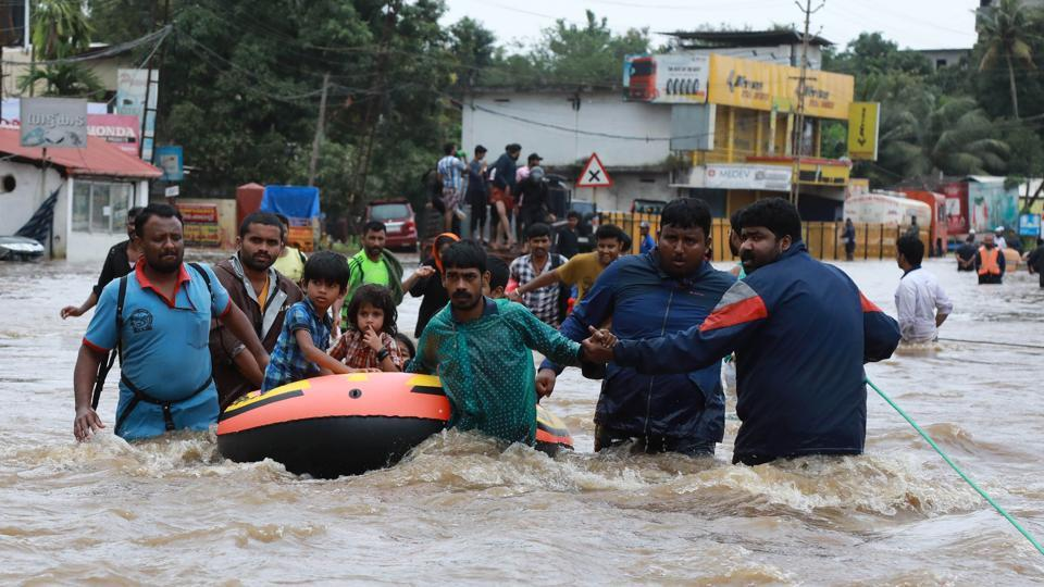 Volunteers and rescue personal evacuate local residents in a boat in a residential area at Aluva in Ernakulam district, Kerala, on August 17, 2018.