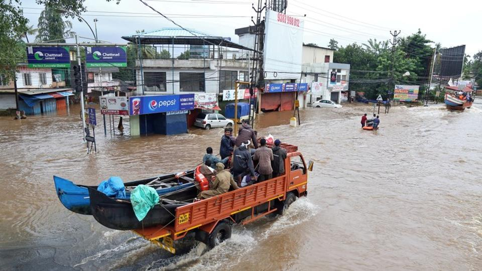 A supply truck transporting boats to flooded areas moves through a water-logged road in Aluva in Kerala.