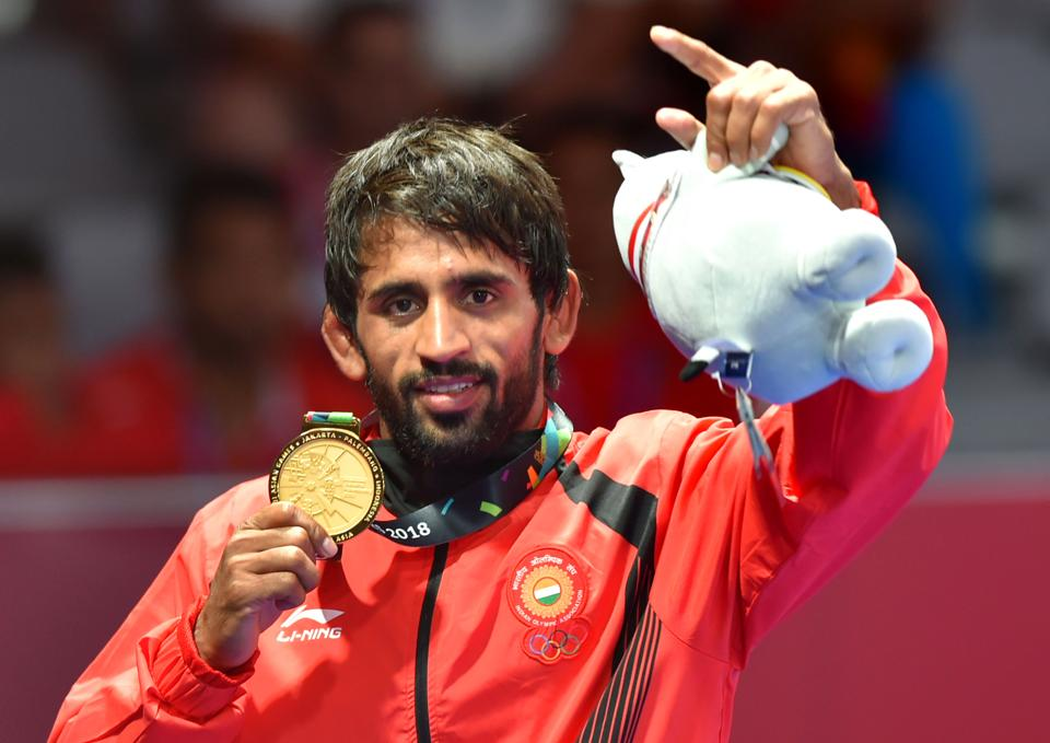 Jakarta: India's Bajrang Punia poses with his gold medal after winning in the Finals of men's freestyle wrestling (65kg) against Japan's Daichi Takatani at the Asian Games 2018, in Jakarta on Sunday, August 19, 2018. (PTI Photo/Shahbaz Khan) (PTI8_19_2018_000227B) (PTI)