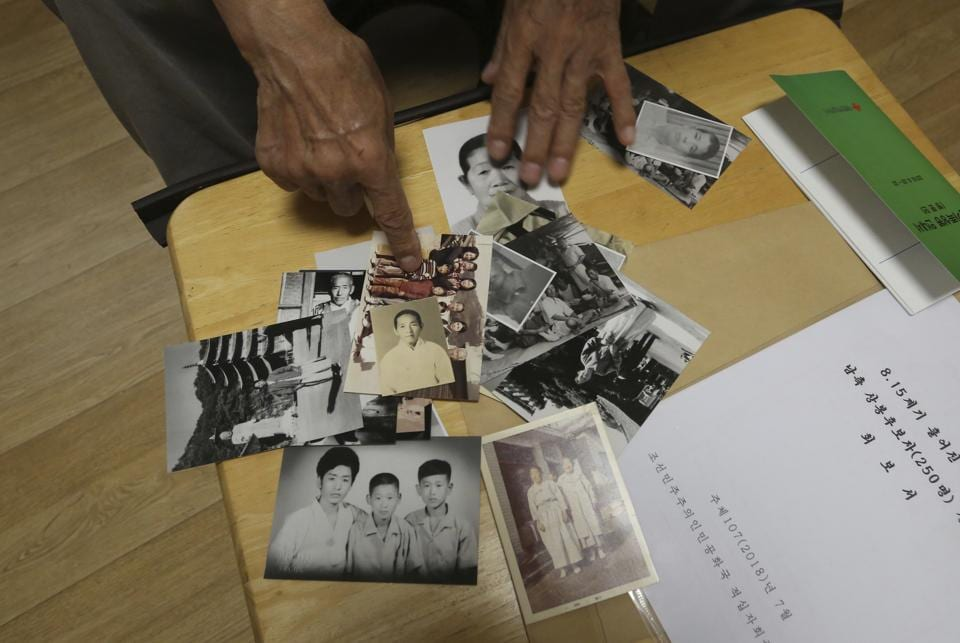 Lee Soo-nam, 76, shows photos of his family members at his home in Seoul, South Korea. Lee is among about 200 war-separated South Koreans and their family members who are crossing into North Korea for heart-wrenching meetings with relatives torn apart by the 1950-53 Korean War they haven't seen for decades. (Ahn Young-joon / AP)