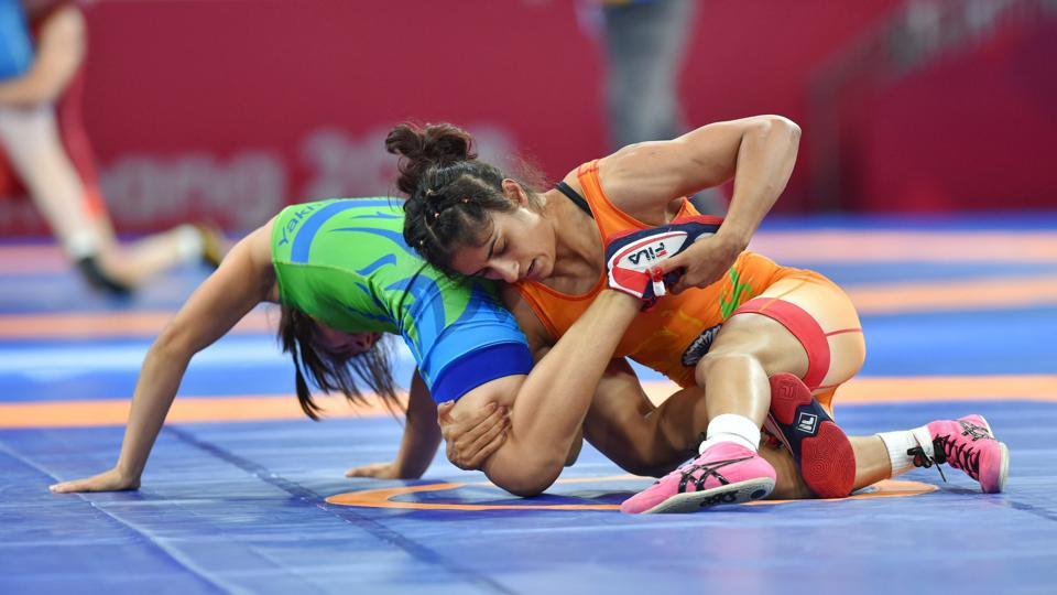 Vinesh Phogat of India (in orange) grapples Uzbekistan's D Yakhshimuratova in the semi-finals of women's 50kg freestyle wrestling event at Asian Games 2018, in Jakarta. Phogat won her bout in little over a minute to storm into the title round, beating Yakhshimuratova by technical superiority. (Shahbaz Khan / PTI)