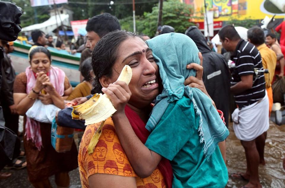 A woman cries as she holds her son after they were evacuated from a flooded area in Aluva, Kerala, on August 18, 2018. As of Tuesday there are a total of 10,28,073 people in 5,645 relief camps across the state of Kerala since the start of the rains. As rains and floodwaters begin receding from many areas in Kerala, rescue operations are scaling down and said to be in their final stages. (Sivaram V / REUTERS)