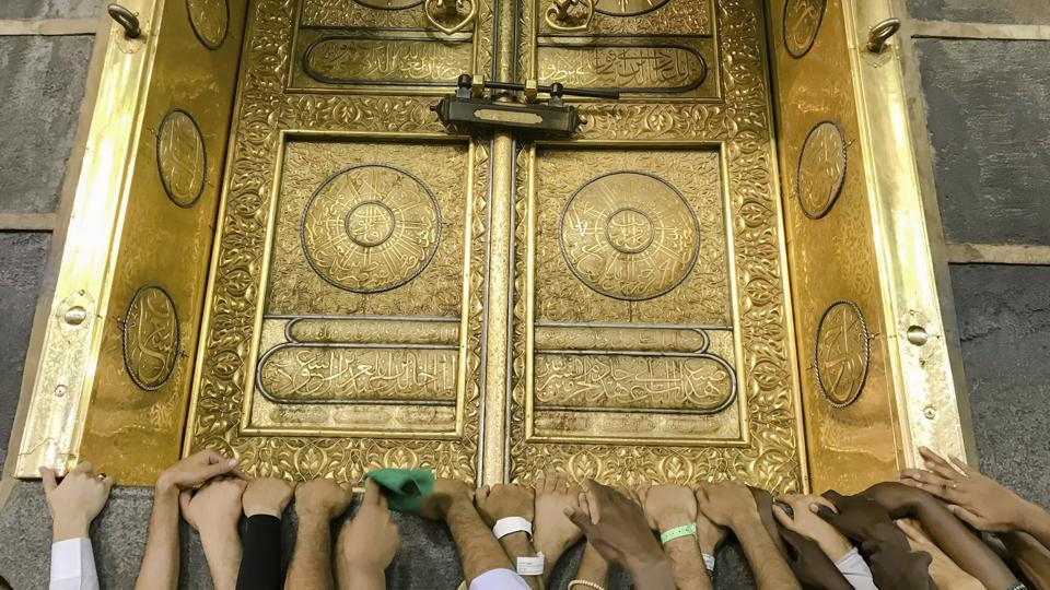 Pilgrims touch the golden door of the Kaaba, the cubic building at the Grand Mosque. For the Muslim faithful, Hajj retraces the last steps of the Prophet Mohammed and also honours the prophets Abraham and Ishmael. (Dar Yasin / AP)