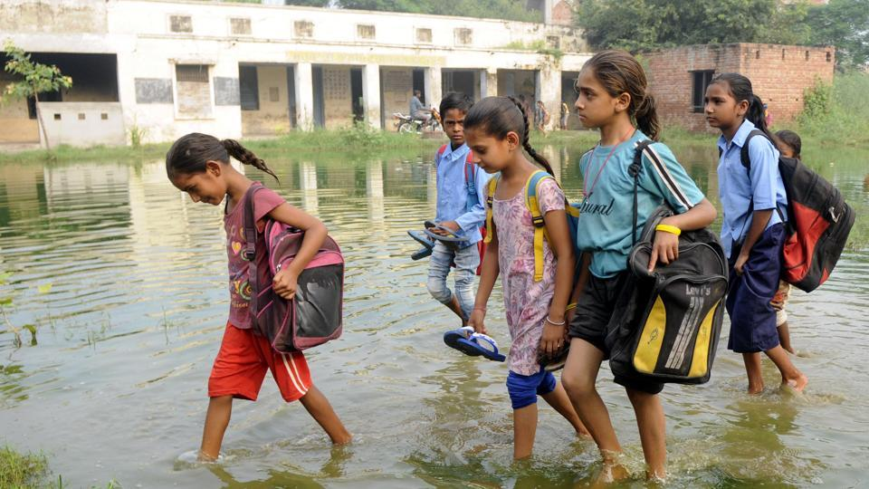 Children walking through a ground inundated with overflow from a septic tank to reach Government Elementary School on the outskirts of Kalar Bheni village, 12km from Patiala, on Tuesday. This has been their routine for the past one month.