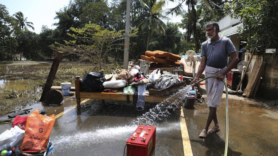 A resident cleans household goods salvaged from sludge in his flood affected house on the outskirts of Kochi on August 21.