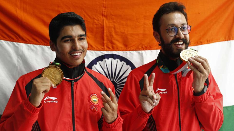 Gold medallist Saurabh Chaudhary of India and bronze medallist Abhishek Verma of India hold up their medals.