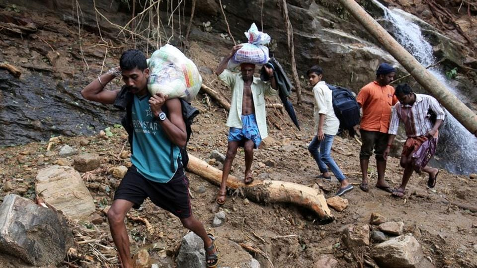 Flood victims carry relief material as they walk through a damaged area after floods, at Nelliyampathy village in Kerala.