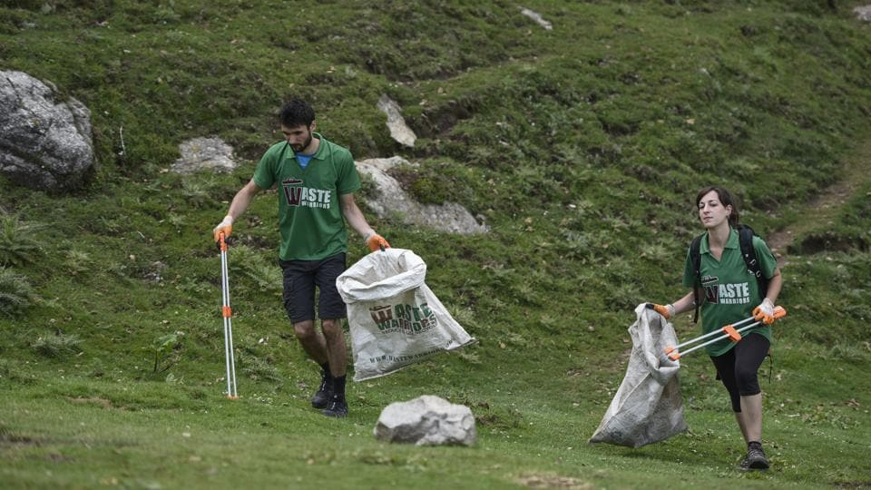 Waste Warriors armed with tongs and sacks during a cleanup drive on the Triund mountains. The challenges that the Triund trail and campsite face are not an exception; popular trails in other states too grapple with similar waste issues. (Burhaan Kinu / HT Photo)