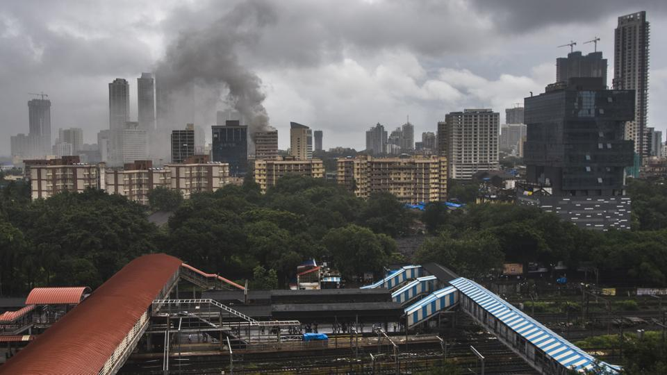 Four people were killed and at least 16 injured in a major fire at the Crystal Tower residential apartments near Hindmata Cinema in Mumbai's Parel area on Wednesday. Rescuers faced a tough time to evacuate people from the 12th floor, where the fire broke out, and floors above as billowing smoke blocked all staircases and other exits, while the building's own fire fighting system was not working. (Pratik Chorge / HT Photo)