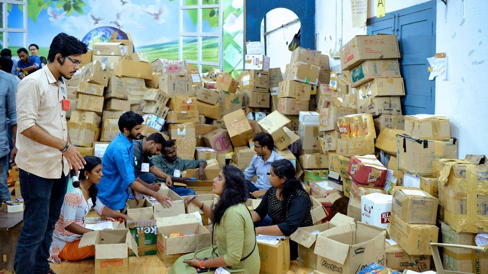 Student volunteers manage and take stock of packed relief material for flood victims at a relief material collection centre in Trivandrum, Kerala.