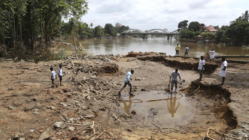 People assess damage caused by floods on the outskirts of Kochi in Kerala on Wednesday.