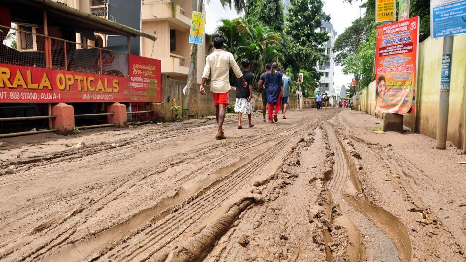 People walk along a muddy road in Kochi, Kerala, August 20, 2018