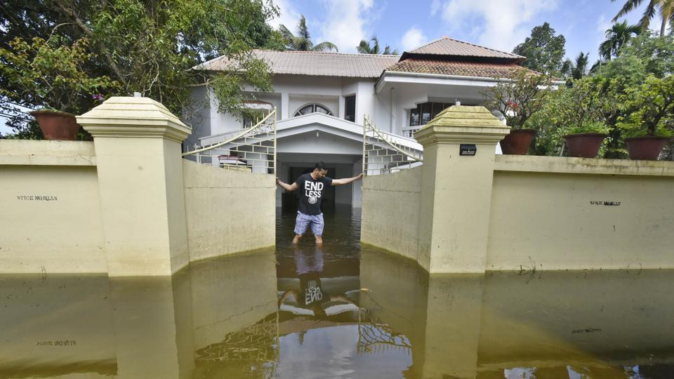 A man closes the gate of his house submerged in flood waters in the outskirts of Alappuzha district, in Kerala. Digital payment provider Paytm collected Rs 30 crore from its 12 lakh users in a week for relief work to flood-hit victims. The armed forces started scaling down rescue operations on Tuesday. (Raj K Raj / HT Photo)