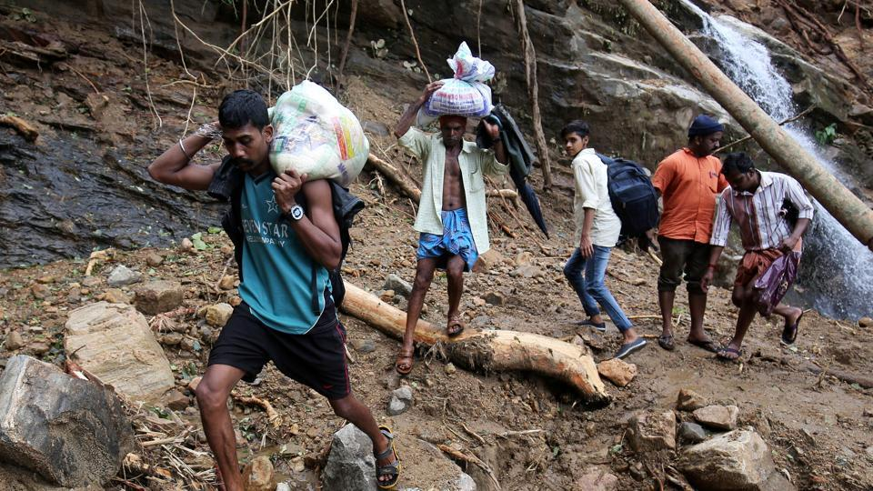 Flood victims carry relief material as they walk through a damaged area after floods, at Nelliyampathy village in Kerala on August 21.