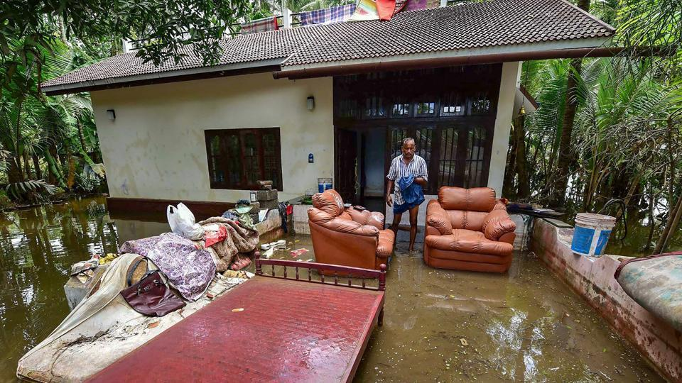 A man cleans up his house after flood water subsides, in Puthenvelikkara near Kochi.