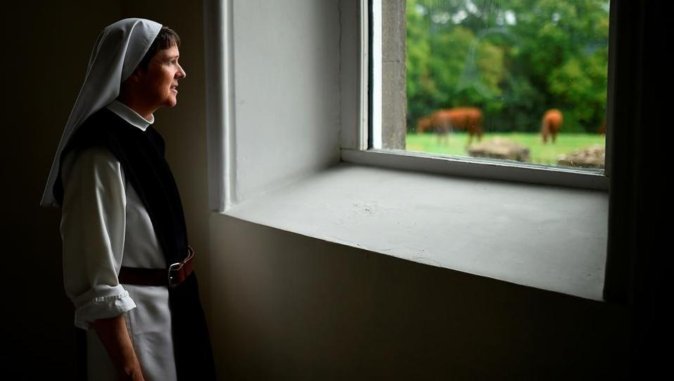 "Sister Angela Finegan looks out of the church window at St Mary's Abbey in Glencairn, Ireland. ""I am so excited about the day, to be in the presence of this good and holy leader of our Church... It will be a great joy and blessing. Especially in the days when the presence of God and the life of the Church are hidden in our fast-paced society,"" said Sister Angela. (Clodagh Kilcoyne / REUTERS)"