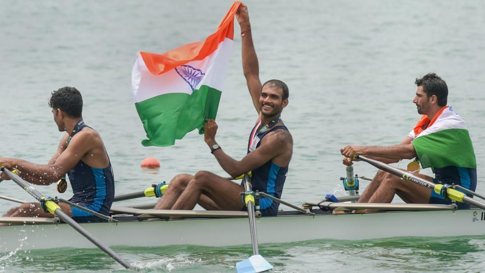 Palembang: Indian rowing Men's team member Bhokanal Dattu holds the national flag as he celebrates after the medal ceremony winning the gold medal Men's Quadruple Sculls. (PTI)
