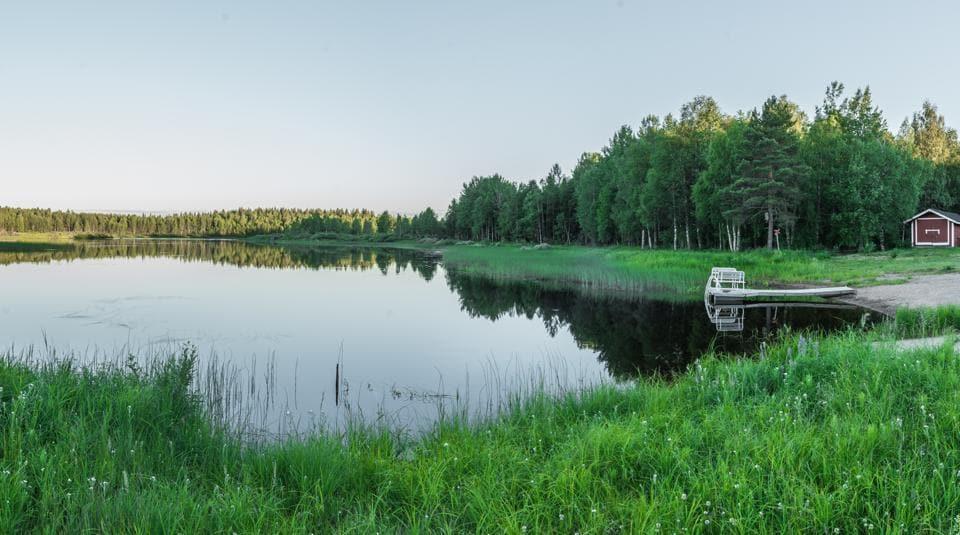 A midnight shot of a cabin at Vikajärvi Lake, Rovaniemi, Finland.