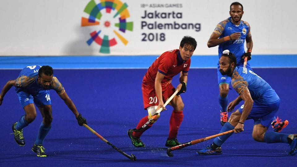 India's Lalit Kumar Upadhyay (L) and Japan's Masaki Ohashi (C) compete for the ball during the men's hockey pool B match. (AFP)