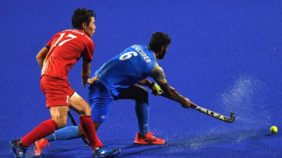 India's Surender Kumar (R) and Japan's Kentaro Fukuda (L) compete for the ball during the men's hockey pool B match between India and Japan. (AFP)