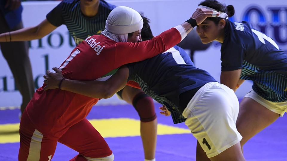 Iran's Ghazal Khalaj (L-in red) tries to a score as India's players defend during the women's team kabaddi final match between India and Iran. (AFP)