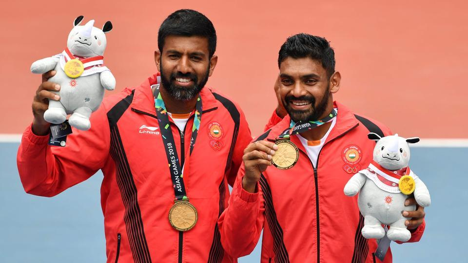 India's gold medallists Divij Sharan (R) and Rohan Bopanna (L) pose for photographers during the medal ceremony for men's doubles tennis at the 2018 Asian Games (AFP)
