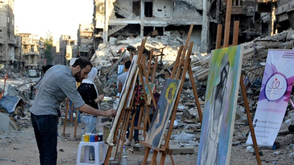 "One painting depicted streams of red running down a dark building and in another; an emaciated man was curled up naked in the foetal position. Visiting the camp last month, UNRWA commissioner-general Pierre Krahenbuhl said he had rarely seen such damage. ""The scale of the destruction in Yarmuk compares to very little else that I have seen in many years of humanitarian work in conflict zones,"" he said. (Maher Al Mounes / AFP)"