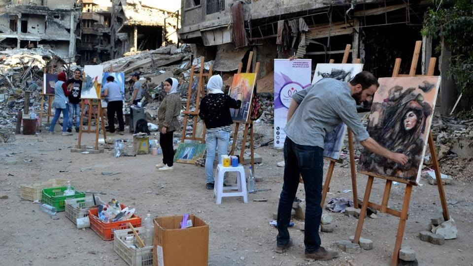 Artists paint in the Yarmuk refugee camp on the southern outskirts of Damascus. Before the war, Yarmuk was home to around 160,000, the United Nations says. Set up in 1957 to house Palestinian refugees, over the decades it became a crowded district that was eventually swallowed up by Damascus. Today, it lies almost deserted. (Maher Al Mounes / AFP)