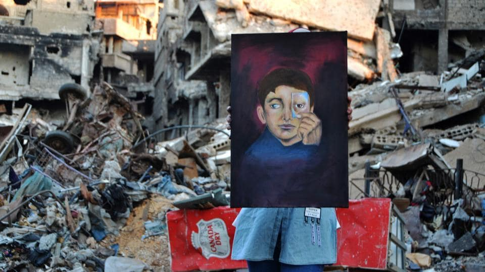 "Painter Hinaya Kebabi depicted a young boy with a missing eye, holding up a drawing of another eye to conceal his wound, the 22-year-old explained. ""One day, I hope people will come back here to colour, not rubble,"" she said. (Maher Al Mounes / AFP)"