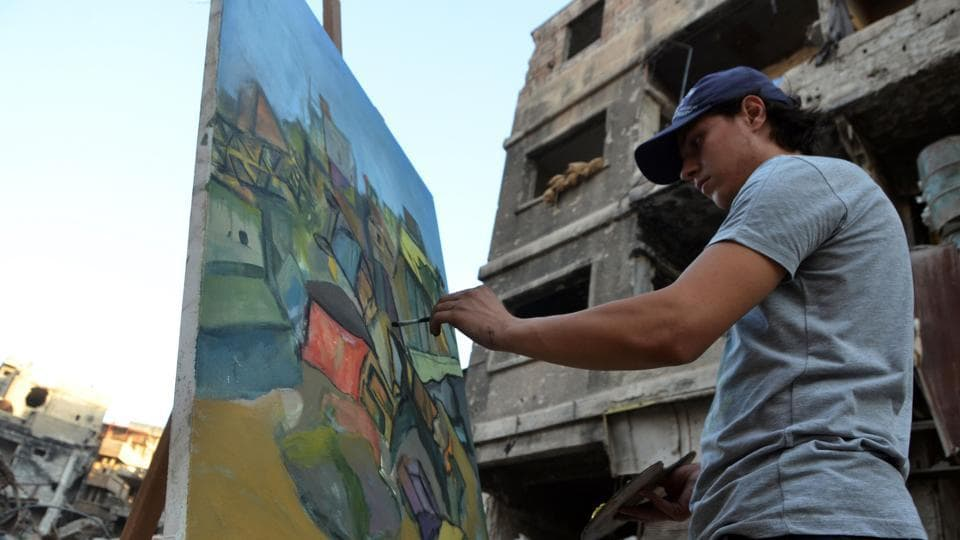 Equipped with paint brushes and pencils, around 12 young artists were seen with their easels in the once-crowded camp turned Damascus suburb, now largely abandoned after seven years of civil war. They set out to translate suffering into art in a neighbourhood ravaged by years of bombardment and siege. (Maher Al Mounes / AFP)