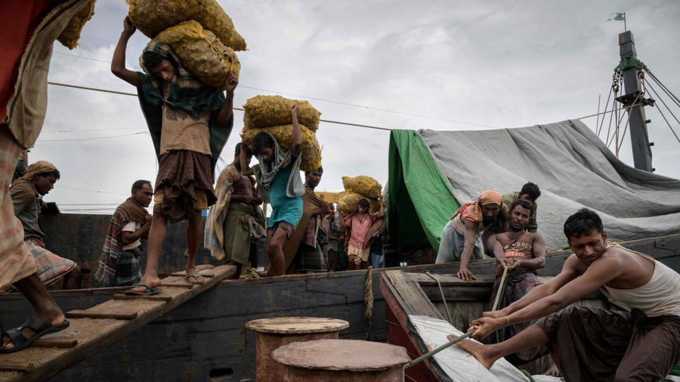 """Captain Min Min, a Buddhist from Myanmar, looks on as a stream of Muslim Rohingya labourers zig-zag up narrow gangplanks hauling sacks of ginger from his boat onto Bangladeshi soil -- one of many seizing the economic opportunities presented by a refugee crisis. """"I don't worry about conflict... everything is just business,"""" the ethnic Rakhine skipper said waiting for his nine-tonne cargo to be unloaded. (Ed Jones / AFP)"""