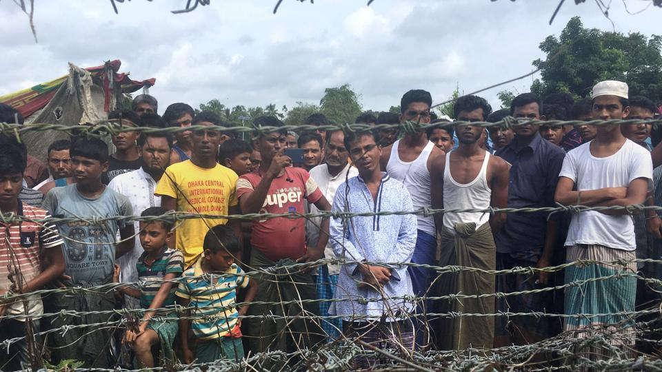 Rohingya refugees gather near the fence in the