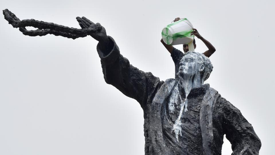 A Congress supporter washes Rajeev Gandhi's statue with milk on the eve of his 74th birth anniversary near Parliament street on August 19, 2018 in New Delhi, India. (Sonu Mehta / HT Photo)
