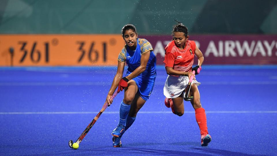 India's Reena Khokhar (L) runs with the ball past Indonesia's Yuanita Suwito during the women's hockey pool B match between India and Indonesia at the 2018 Asian Games in Jakarta on August 19, 2018. (Punit Paranjpe / AFP)