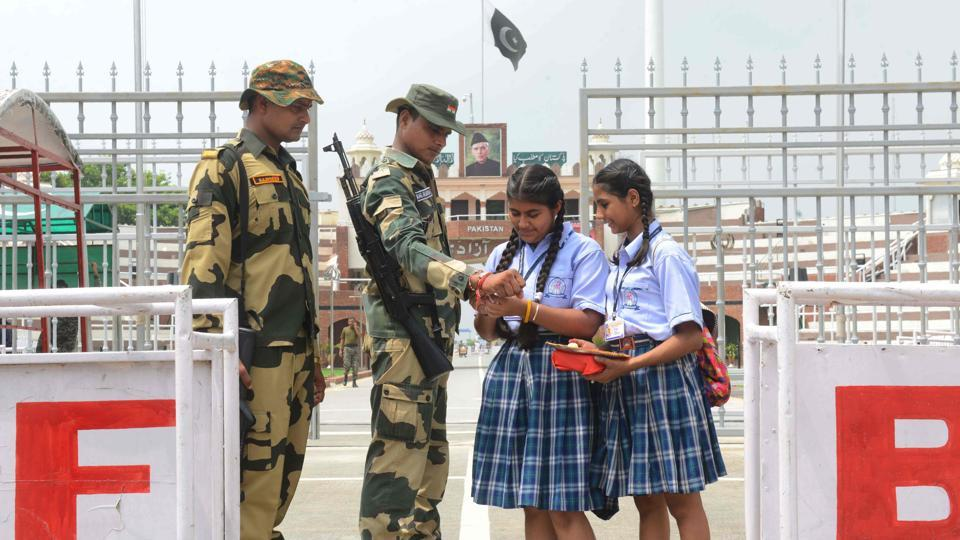 School girls tie a rakhi onto the wrists of Border Security Force (BSF) personnel during celebrations ahead of the Raksha Bandhan festival, on August 23, 2018 at the India-Pakistan Wagah Border Post about 35kms from Amritsar, Punjab. (Narinder Nanu / AFP)