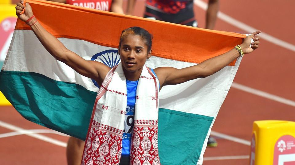 Indian athlete Hima Das holds the Indian tricolour after securing silver medal in the women's 400m final on Athletics track event. (PTI)