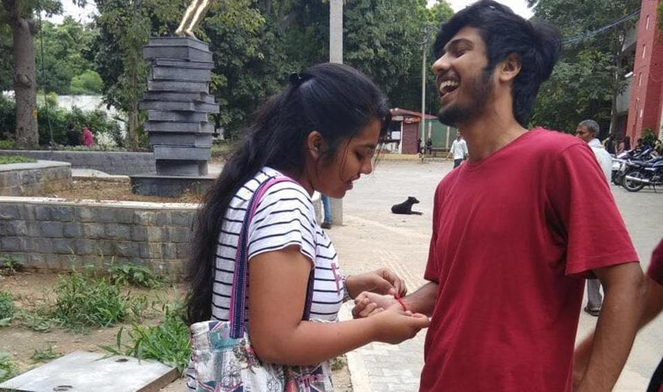 A girl ties rakhi to a college friend.
