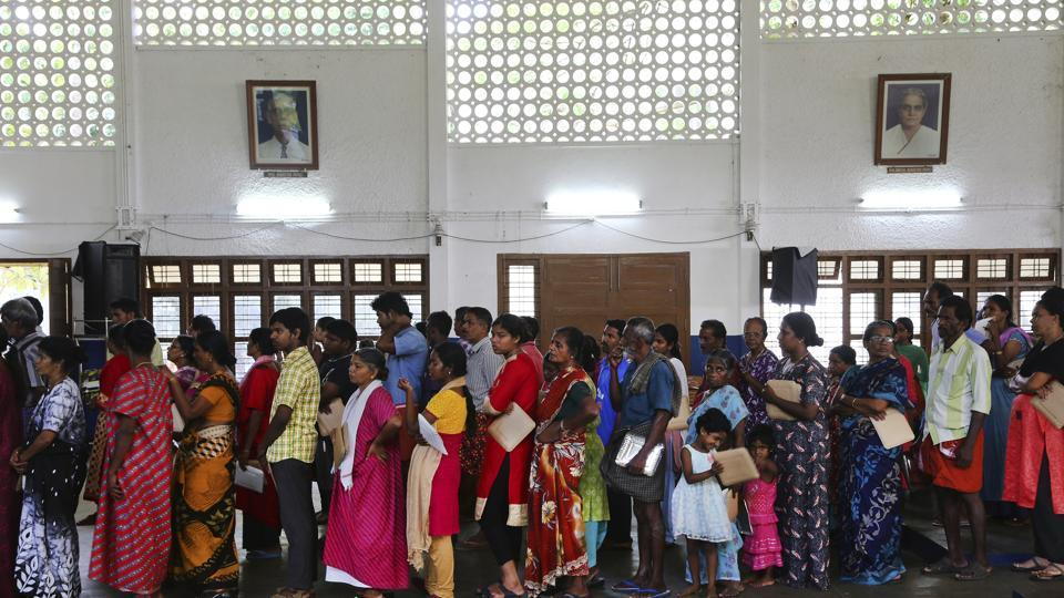 Flood affected victims stand in a queue for food at a relief camp set up inside a school in Kochi on August 23.