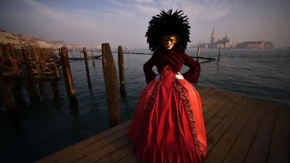 A masked reveller poses at St Mark's Square in Venice during this year's Venice Carnival.