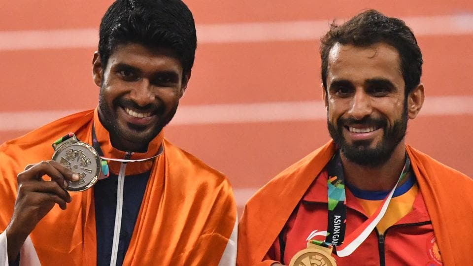 (L-R) Silver medallist India's Jinson Johnson and gold medallist India's Manjit Singh celebrate during the victory ceremony for the men's 800m athletics. (AFP)