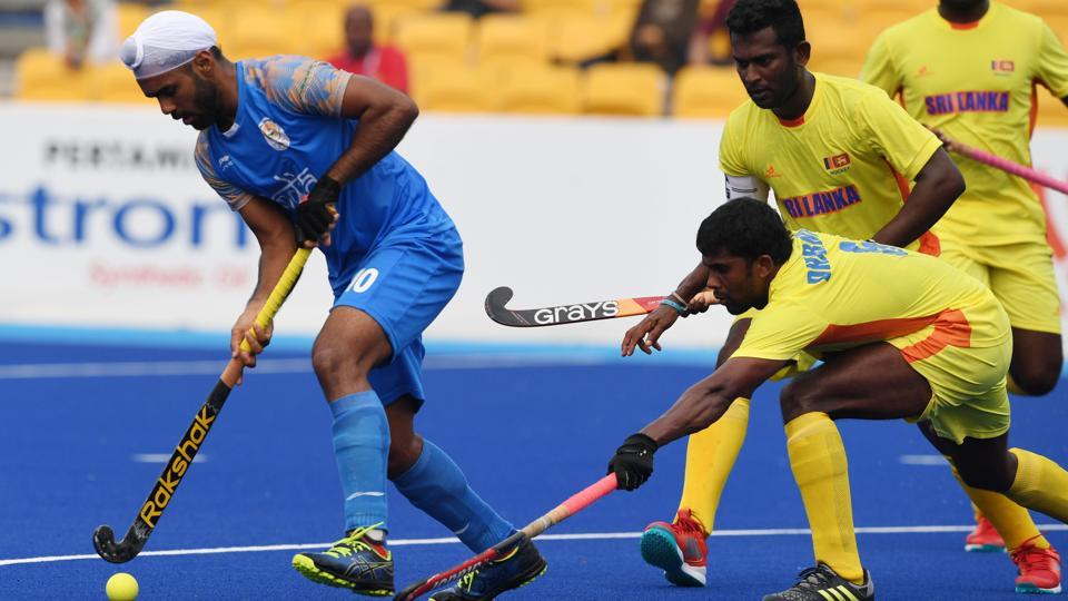 India's Simranjeet Singh (L) controls the ball as Sri Lanka's Meegahamulla Gedara H. Dharmarathne (bottom R) during the men's hockey pool A match between India and Sri Lanka. (AFP)
